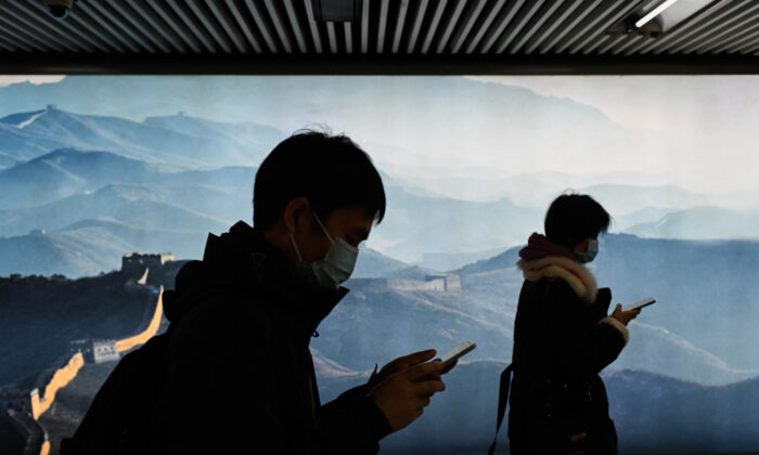 A man and a woman wearing face masks use their mobile phone as they walk in a subway station in Beijing on March 11, 2020. (Wang Zhao/AFP via Getty Images)