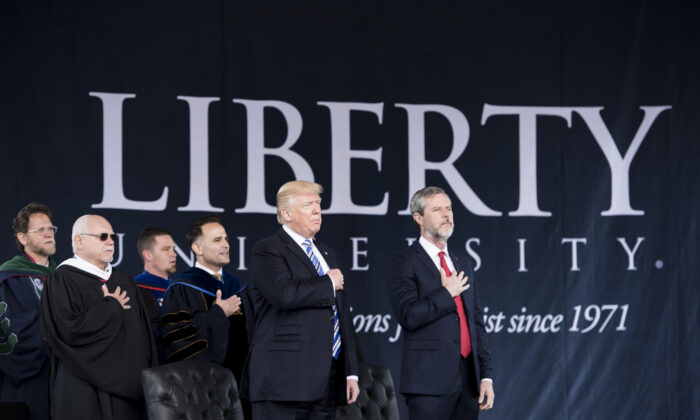 President Donald Trump (2nd R), President of Liberty University Jerry Falwell (R), and others participate in the Pledge of Allegiance during Liberty University's commencement ceremony in Lynchburg, Virginia, on May 13, 2017. (Brendan Smialowski/AFP via Getty Images)