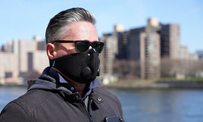 A man walks by the East River wearing a protective mask as the coronavirus continues to spread across the United States, in New York City on March 22, 2020. (Cindy Ord/Getty Images)