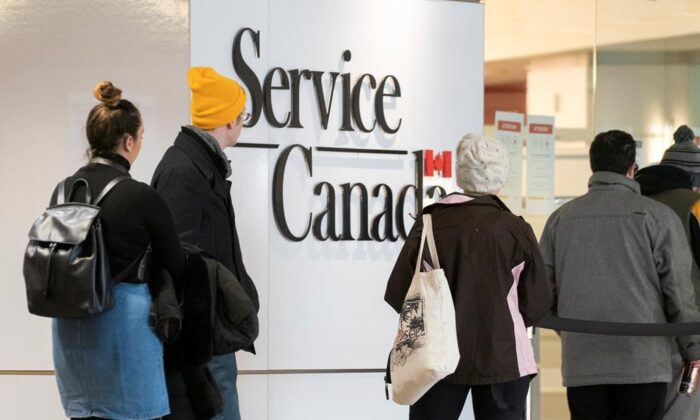 People line up at a Service Canada office in Montreal on March 19, 2020. Canadians who have lost their jobs due to COVID-19 and are struggling to make ends meet are anxiously awaiting federal help from an emergency $82-billion financial package passed by the House of Commons on Wednesday. (Paul Chiasson/The Canadian Press)