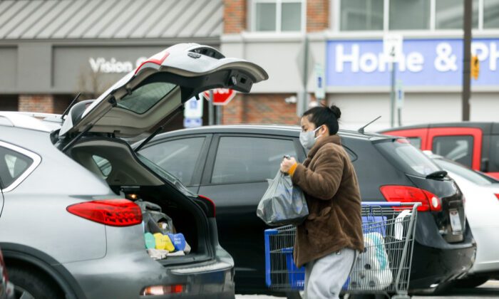A woman with a face mask loads her groceries in a Walmart carpark in Columbus, Ohio, on March 20, 2020. (Charlotte Cuthbertson/The Epoch Times)