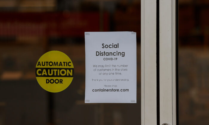 A sign about social distancing is seen at the entrance of The Container Store near Perimeter Mall in Atlanta, Georgia on March 20, 2020. (Kevin C. Cox/Getty Images)