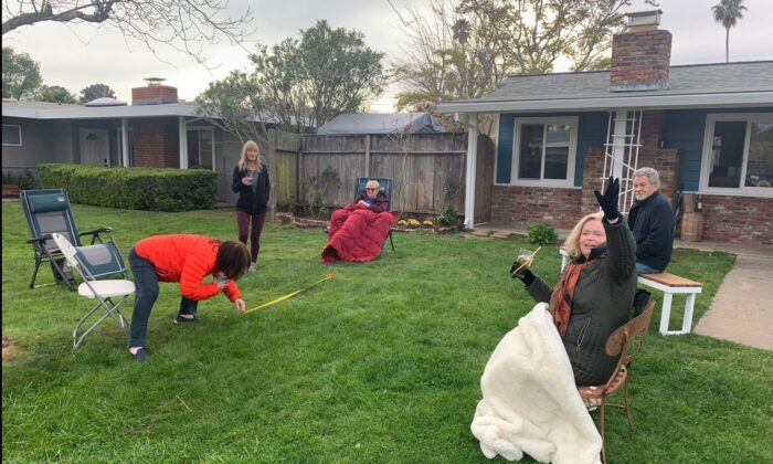 """The song """"I will survive"""" plays aloud as friendly neighbors hold a six-foot party on their lawn where each of them stays at least six feet away from each other in Mill Valley, Calif., on March 17, 2020. (Josh Edelson/AFP via Getty Images)"""