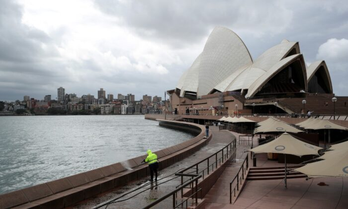 A worker cleans the waterfront area of the Sydney Opera House, in the wake of New South Wales implementing measures shutting down non-essential businesses and moving toward harsh penalties to enforce self-isolation, in Australia on March 26, 2020. (Loren Elliott/Reuters)