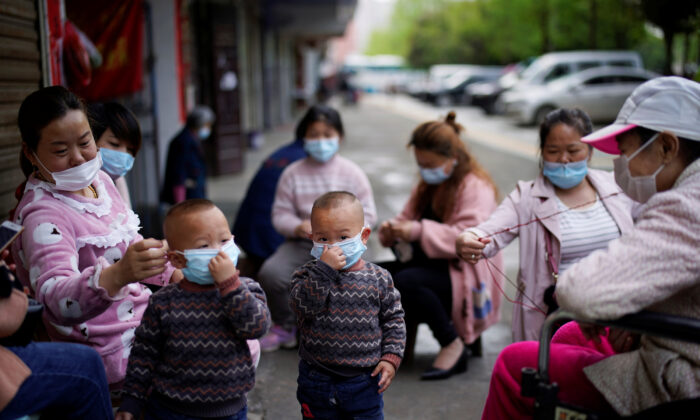 Children and women wearing face masks are seen in Xianning, after the lockdown was eased in Hubei Province, the epicenter of China's coronavirus disease (COVID-19) outbreak, on March 26, 2020. (Aly Song/Reuters)