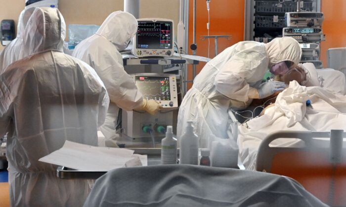 A medical worker in protective gear (R) tends to a patient at the new COVID 3 level intensive care unit for COVID-19 cases at the Casal Palocco hospital near Rome, Italy, on March 24, 2020. (Alberto Pizzoli/ AFP via Getty Images)