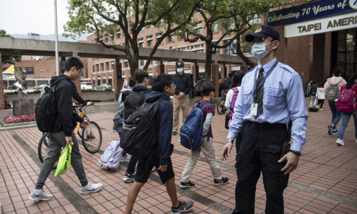 Students enter the Taipei American School in Taipei, Taiwan, on March 18, 2020. Taiwan, Singapore, and Hong Kong have had more success in battling the COVID-19 pandemic that other jurisdictions can learn from. (Paula Bronstein/Getty Images)