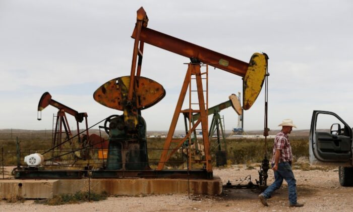 Paul Putnam, 53, a rancher and independent contract pumper walks past a pump jack in Loving County, Texas on Nov. 25, 2019. (Angus Mordant/Reuters)