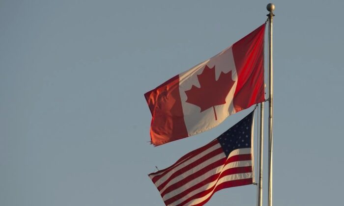The Canadian and American flags are seen on top of the Peace Arch at the Canada-U.S. border in Surrey, B.C., on March 20, 2020. (Jonathan Hayward/The Canadian Press)