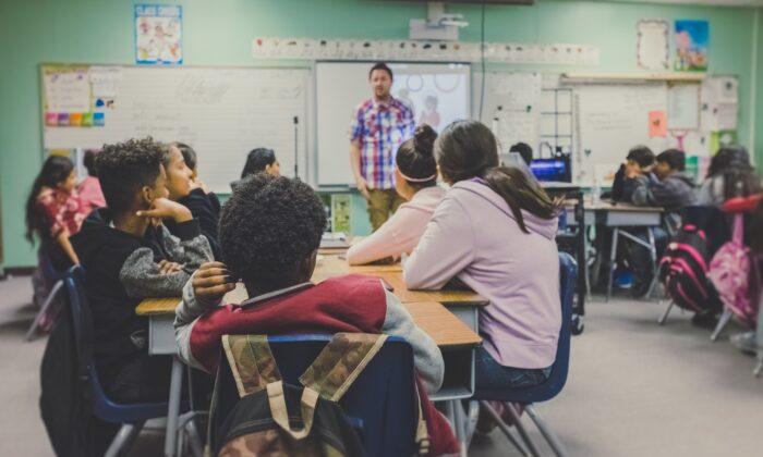 Children listen to a teacher in a classroom. (Photo by NeONBRAND on Unsplash)