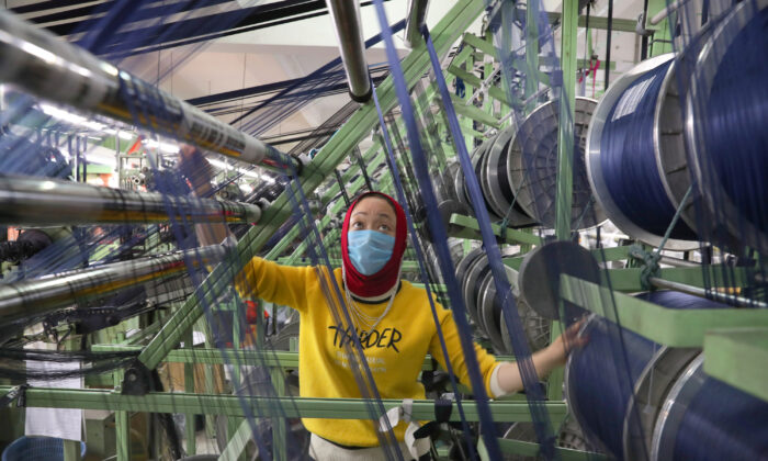 An ethnic minority employee wearing a face mask works on a production line manufacturing elastic fabric products, as the country is hit by an outbreak of the novel coronavirus disease (COVID-19), in Nantong, Jiangsu Province, China, on (March 26, 2020. China Daily via Reuters)