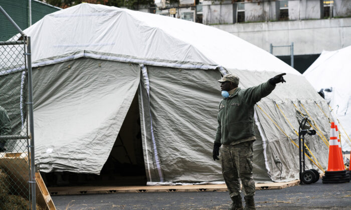 An Air Force member gives instructions as workers and members of the National Guard build a makeshift morgue outside Bellevue Hospital in New York City on March 25, 2020. (Eduardo Munoz Alvarez/Getty Images)