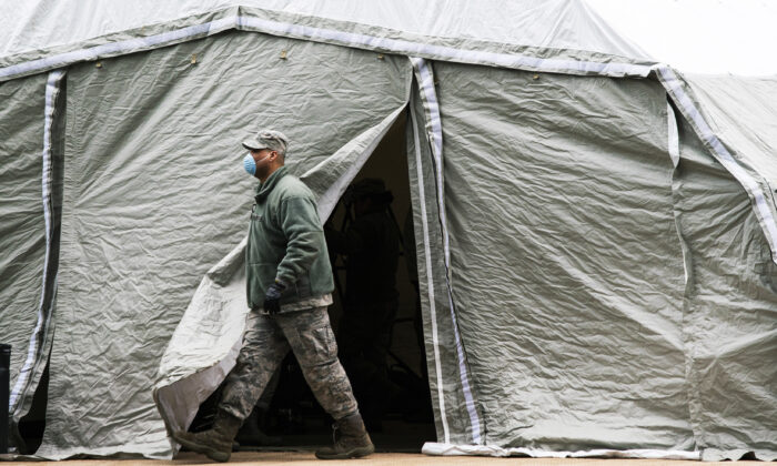 An Air Force member exits a tent erected as a makeshift morgue outside of Bellevue Hospital in New York City on March 25, 2020. (Eduardo Munoz Alvarez/Getty Images)