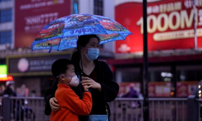 People wearing face masks walk in Jingzhou, after the lockdown was eased in Hubei Province, the epicenter of China's coronavirus disease (COVID-19) outbreak, on March 26, 2020. (Aly Song/Reuters)