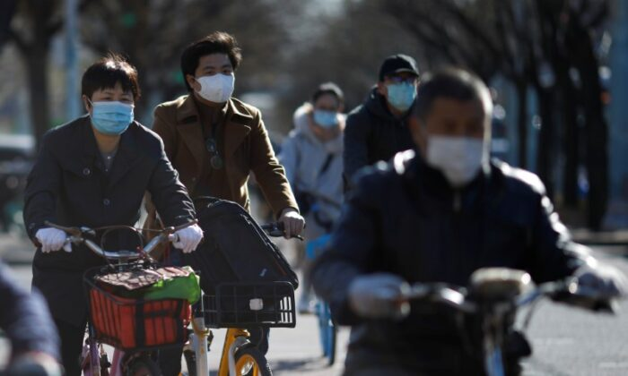 People wearing face masks ride bikes following an outbreak of the CCP Virus, in Beijing, China, March 27, 2020. (Reuters/Carlos Garcia Rawlins)