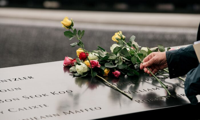 Relatives of the 1993 World Trade Center bombing victims place roses over a plaque etched with victims' names during a ceremony in New York City on Feb. 26, 2020. (Scott Heins/Getty Images)