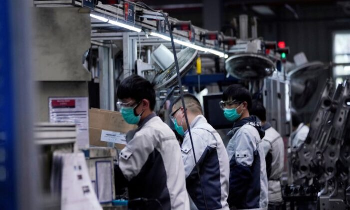 Employees wearing face masks work on a car seat assembly line at Yanfeng Adient factory in Shanghai, China, as the country is hit by an outbreak of a new coronavirus, on Feb. 24, 2020. (Aly Song/Reuters)