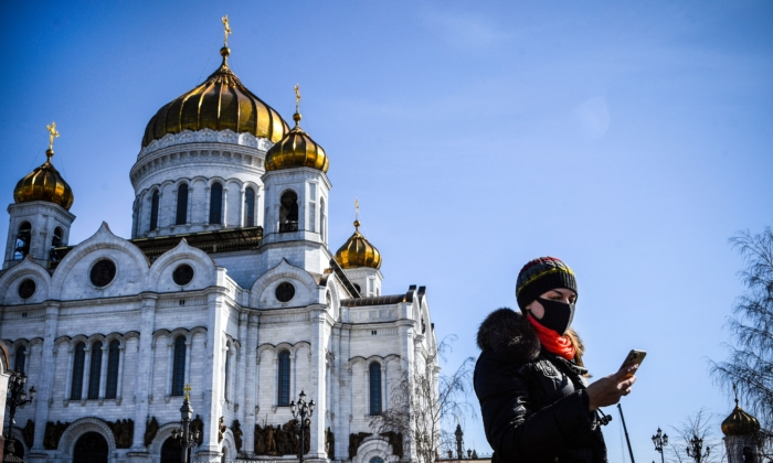 A woman wearing a face mask, amid concerns over the spread of the CCP virus, walks past the Cathedral of Christ the Saviour in downtown Moscow on March 26, 2020. (ALEXANDER NEMENOV/AFP via Getty Images)