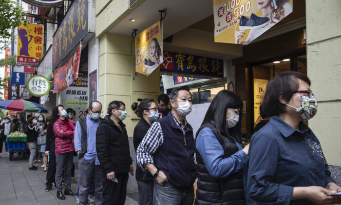 People wait in line at a pharmacy to pick up masks pre-ordered online, in Taipei, Taiwan, on March 18, 2020. (Paula Bronstein/Getty Images )