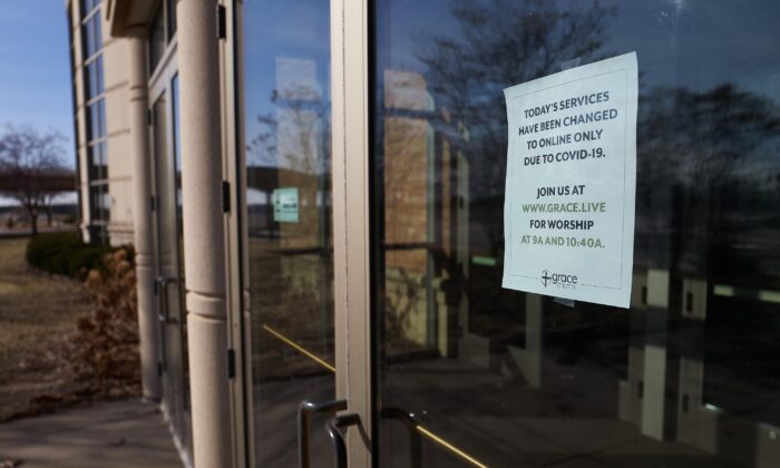 A sign on the door to Grace Church Eden Prairie pointed churchgoers to online services after church leadership decided to present worship music and the sermon to an estimated 3,500 online viewers in Eden Prairie, Minnesota, on March 15, 2020. (Adam Bettcher/Getty Images)