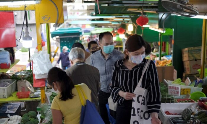 People with protective masks walk at a market at the financial Central District, following the novel coronavirus disease (COVID-19) outbreak, in Hong Kong, China, on March 27, 2020. (Tyrone Siu/Reuters)