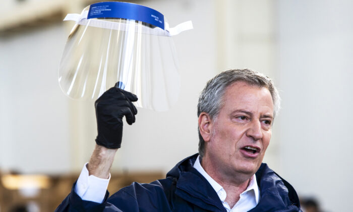 New York City Mayor Bill de Blasio holds a face shield as he speaks to the media during a visit to the Brooklyn Navy Yard where local industrial firms have begun manufacturing Personal Protective Equipment (PPE) in New York CIty on March 26, 2020. (Eduardo Munoz Alvarez/Getty Images)