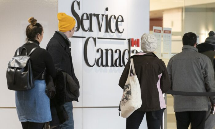 People line up at a Service Canada office in Montreal, Canada, on March 19, 2020. (Paul Chiasson/The Canadian Press)