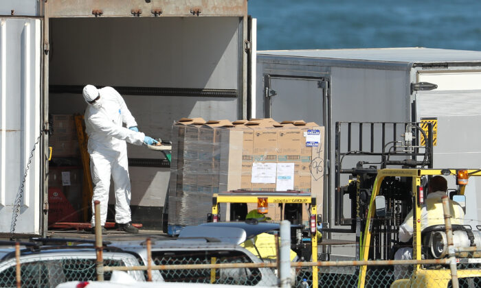 Workers are seen unloading supplies from a truck wearing protective equipment to be loaded onto the MSC Magnifica berthed at the Fremantle Passenger Terminal  in Fremantle, Australia, on March 24, 2020. (Paul Kane/Getty Images)