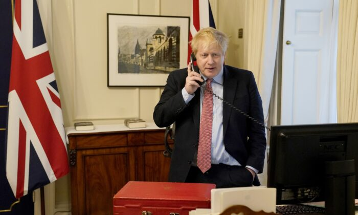 Prime Minister Boris Johnson on the telephone to Queen Elizabeth II for her Weekly Audience during the CCP virus pandemic at 10 Downing Street in London on March 25, 2020. (Andrew Parsons-WPA Pool/Getty Images)