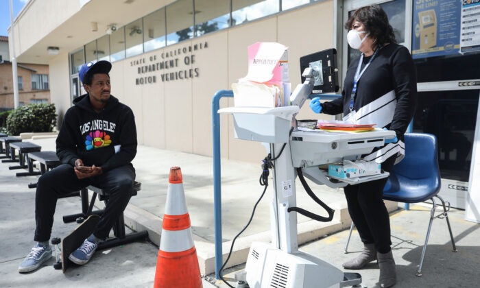 A Department of Motor Vehicles worker (R) speaks with a man who did not have an appointment at an appointment desk in front of the DMV building, with a cone used to implement social distancing in Los Angeles, California, on March 23, 2020. (Mario Tama/Getty Images)