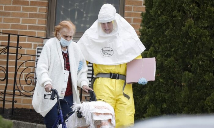 Medical officials aid a resident from St. Joseph's nursing home to board a bus, after a number of residents tested positive for the CCP virus in Woodbridge, New Jersey on March 25, 2020. (Stefan Jeremiah/Reuters)