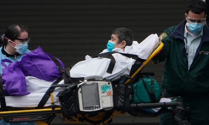 Paramedics move a patient into the hospital during the outbreak of the CCP virus in the Manhattan borough of New York City on March 25, 2020. (Carlo Allegri/Reuters)