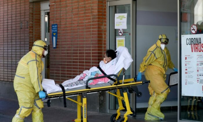 Ambulance workers in full protective gear arrive with a patient at the Severo Ochoa Hospital during the COVID-19 outbreak in Leganes, Spain on March 26, 2020. (Susana Vera/Reuters)