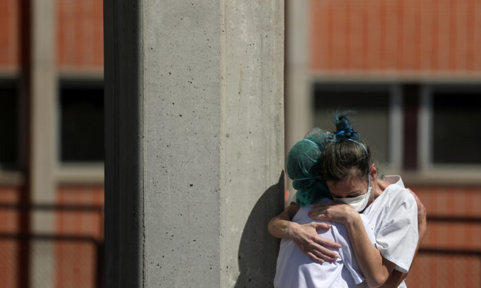 Medical wokers hug each other outside the emergency rooms at Severo Ochoa Hospital during the COVID-19 outbreak in Leganes, Spain on March 26, 2020. (Susana Vera/Reuters)