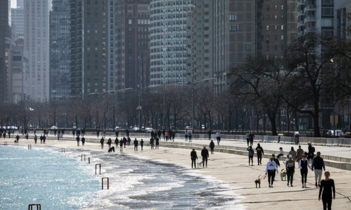 Residents enjoy the warm weather with a stroll along the Lakefront Trail near Oak Street Beach, on March 25, 2020, in Chicago, Illi., despite a stay-at-home order from Illinois Gov. J.B. Pritzker during the CCP virus pandemic. (Ashlee Rezin Garcia/Chicago Sun-Times via AP)
