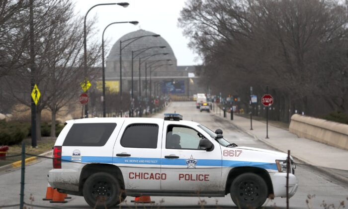 A Chicago police officer blocks the road to the Adler Planetarium along Lake Michigan in Chicago on March 26, 2020. (Charles Rex Arbogast/AP Photo)