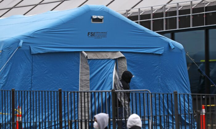 A person emerges from a tent set up in the driveway of the emergency entrance to Elmhurst Hospital Center in New York on March 28, 2020, as others wait in line to be tested for the CCP virus. The hospital is caring for a high number of CCP virus patients in the city. (Kathy Willens/AP Photo)