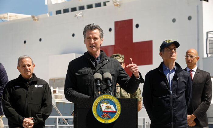 California Gov. Gavin Newsom (C), flanked by (from L) Director Mark Ghilarducci, Cal OES, Los Angeles Mayor Eric Garcetti, and Dr. Mark Ghaly, Secretary of Health and Human Services, speaks in front of the hospital ship USNS Mercy after it arrived into the Port of Los Angeles on March 27, 2020. (Carolyn Cole/Pool/AFP via Getty Images)