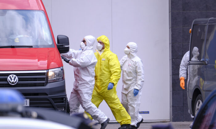 Members of the Emergency Military Unit give instructions to a van driver outside the Palacio de Hielo (Ice Rink), which has been temporarily converted into a morgue with hundreds of bodies of victims of the CCP virus, in Madrid on March 27, 2020. (Xaume Olleros/Getty Images)