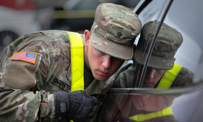 A U.S. National Guard soldier listens to a patient at a drive-thru CCP virus testing center at Lehman College in New York City on March 28, 2020. (John Moore/Getty Images)