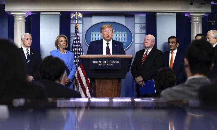 President Donald Trump speaks as Vice President Mike Pence, Secretary of Education Betsy DeVos, and Secretary of Agriculture Sonny Perdue look on during a briefing on the CCP virus pandemic in the press briefing room of the White House in Washington on March 27, 2020. (Drew Angerer/Getty Images)
