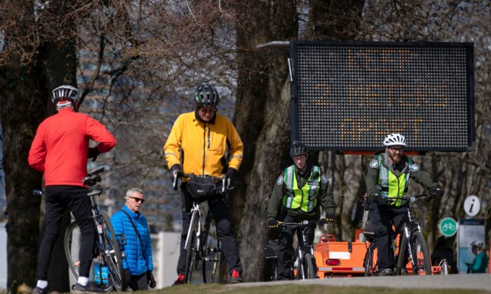 A sign warns people to keep at least 2 metres apart from one another due to concerns about the spread of COVID-19, as park rangers and others bike and walk on the seawall, in Vancouver on March 25, 2020. (The Canadian Press/Darryl Dyck)