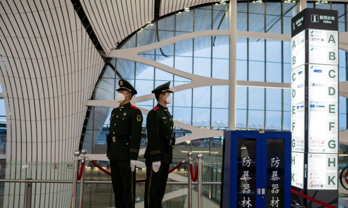 This picture taken on Feb. 14, 2020 shows Chinese paramilitary police officers wearing protective masks as they secure an area at Daxing international airport in Beijing. (Nicolas Asfouri/AFP via Getty Images)