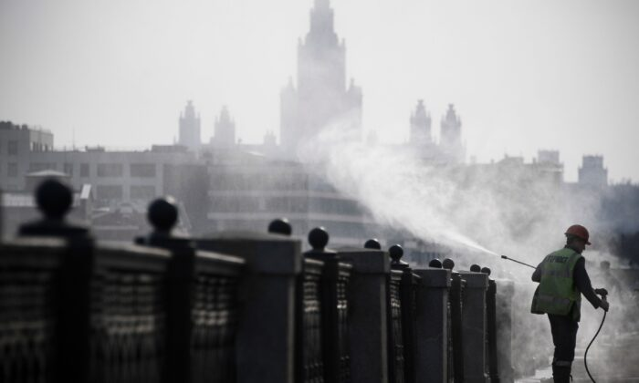 A municipal worker disinfects an embankment fence in Moscow on March 28, 2020, in front of the building of the Moscow State University, as the city attempts to curb the spread of the COVID-19, the disease caused by the CCP virus. (Alexander Nemenov/AFP via Getty Images)
