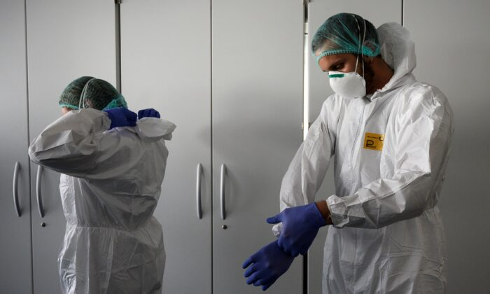Nurses put on their personal protective equipment before starting to work on the preparation of the intensive care unit in the new COVID-19 Hospital in Verduno, near Alba, Northwestern Italy on March 29, 2020. (Marco Bertorello/AFP via Getty Images)