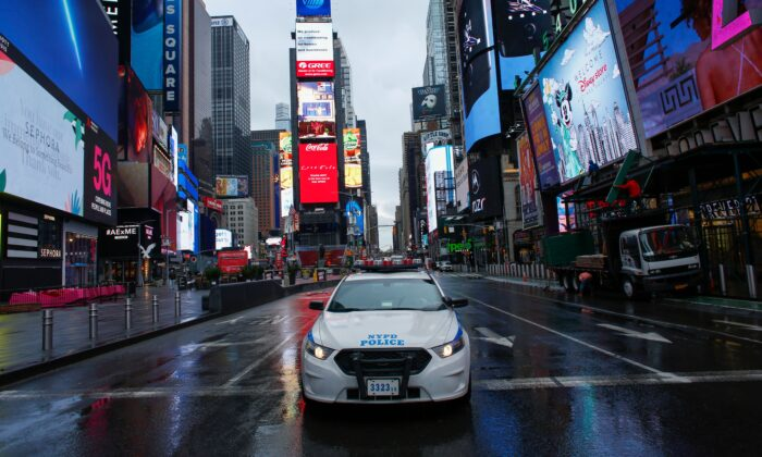 A NYPD car drives by Times Square as rain falls in New York City on March 28, 2020. (Kena Betancur/AFP via Getty Images)