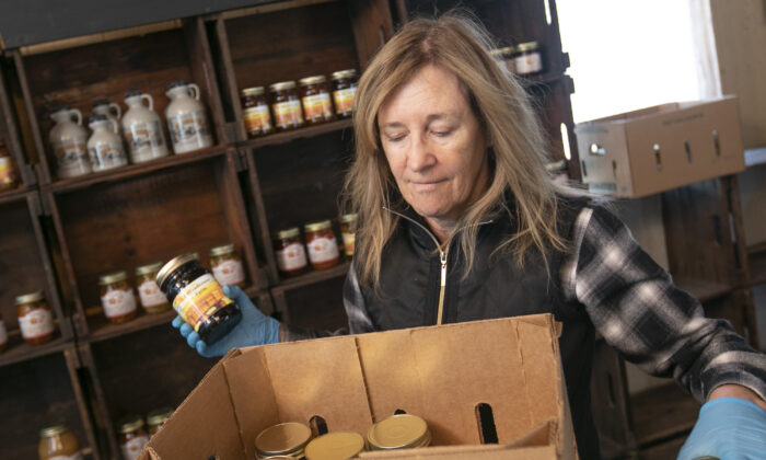 """Linda DeFrancesco stocks shelves with her farm's own salsa, spreads, veggies and salsa at DeFrancesco Farm Stand in Northford, Conn., on March 26, 2020. Businesses across the state are worried about the impact of the coronavirus, even the ones considered """"essential"""" like farmers' markets and garden centers. (Dave Zajac/Record-Journal via AP)"""
