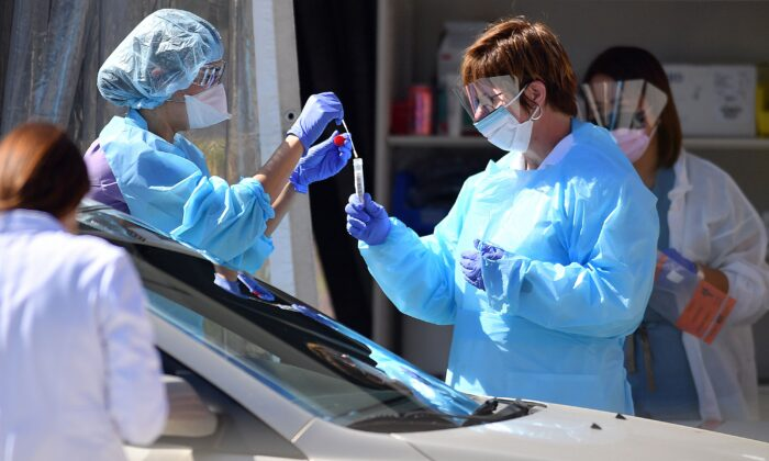 Medical workers at Kaiser Permanente French Campus test a patient for COVID-19 at a drive-thru testing facility in San Francisco, California on March 12, 2020. (Josh Edelson/AFP via Getty Images)