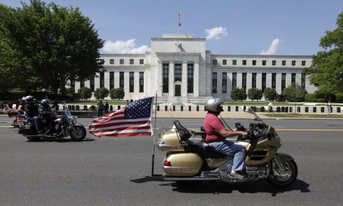 A motorcyclist rides by the Federal Reserve building in Washington, on May 24, 2015. (Chris Kleponis/AFP/Getty Images)