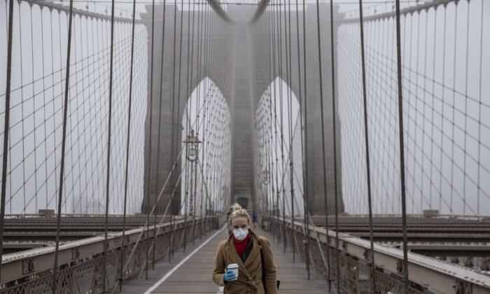 A woman wearing a mask walks the Brooklyn Bridge in the midst of the coronavirus (COVID-19) outbreak in New York City on March 20, 2020. (Victor J. Blue/Getty Images)